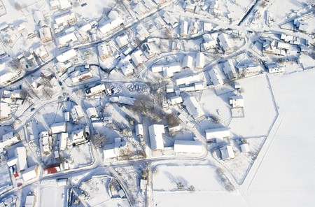 Snow covered winter village in central Europe,air view.