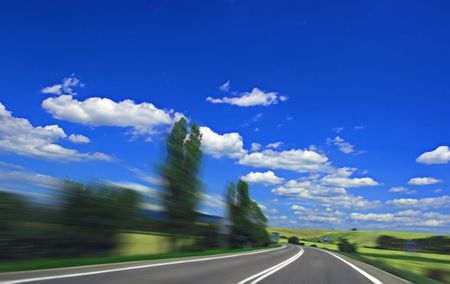 Asphalt highway with motion blur and blue cloudy sky