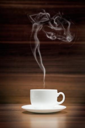 어두운 나무 배경에 여자 모양의 연기와 함께 커피 한잔 스톡 콘텐츠