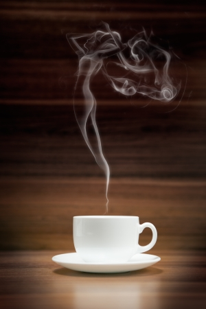 Cup of coffee with woman-shaped smoke on dark wood background