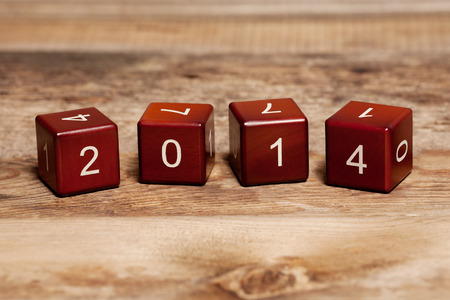 Cubes with numbers isolated on old wooden background  Concept new year 2014  photo