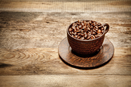 coffeebeans: Wooden cup with coffee-beans on old wooden table. With place for text. Stock Photo