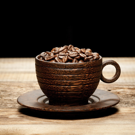 coffeebeans: Wooden cup with coffee-beans on old wooden table Stock Photo