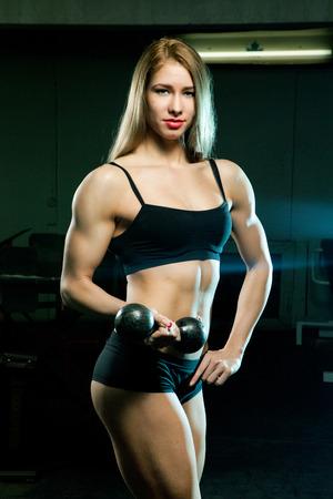 Schöne sportliche muskulöse Frau mit zwei Hanteln in der alten Turnhalle