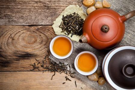 Teetassen mit Teekanne auf alten Holztisch. Draufsicht.
