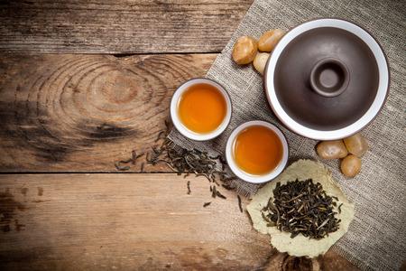 ollas de barro: Tazas de té con la tetera sobre la mesa de madera vieja. Vista superior. Foto de archivo