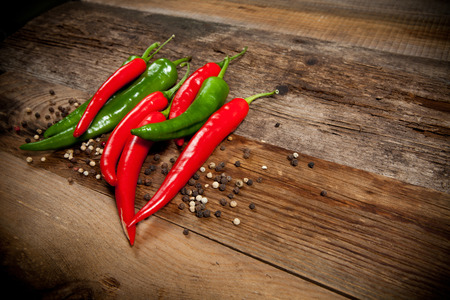 chili peppers: Red hot chili peppers on old wooden table with place for text
