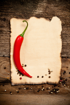 one sheet: One Red Hot Chili Pepper with the Old Paper sheet on old wooden table