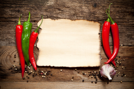 Red Hot Chili Peppers with the Old Paper sheet on old wooden table photo