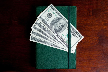 Stacks of one hundred dollars banknotes in notebook on wooden desk photo