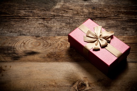 Gift box on old wooden background with place for text