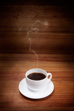 暗い木製の背景に煙とコーヒーのカップ