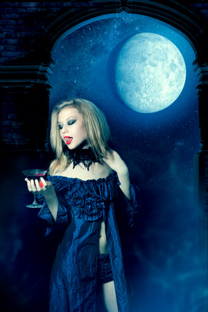 Vampire girl in a dress with glass of wine photo