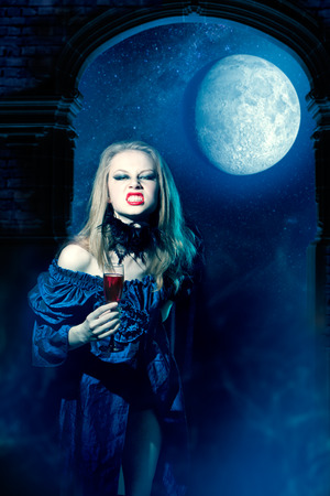 Aggressive vampire girl with glass of wine photo