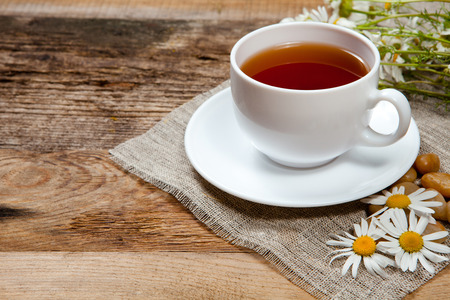 tea light: herbal tea with chamomile on old wooden table