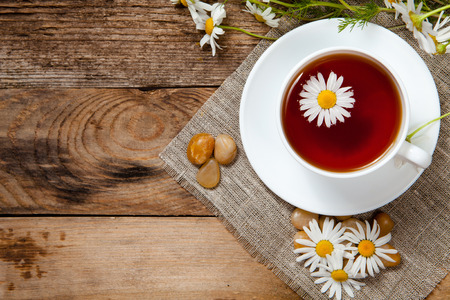 herbal tea with chamomile on old wooden table. Top view. Standard-Bild