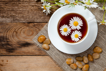 herbal tea with chamomile on old wooden table. Top view. Stock Photo - 29489821