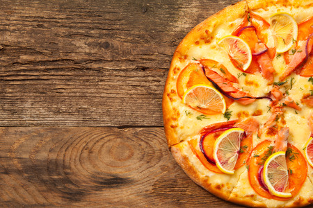 Salmone pizza on old wooden table. Top view with place for text. photo