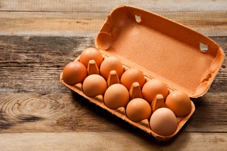 Eggs in the package on wooden table Standard-Bild