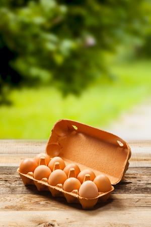 Eier in der Verpackung auf Holztisch auf grünem Hintergrund. Mit Platz für Text.