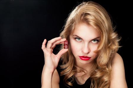 黒の背景に赤のサイコロを持つ若い女性