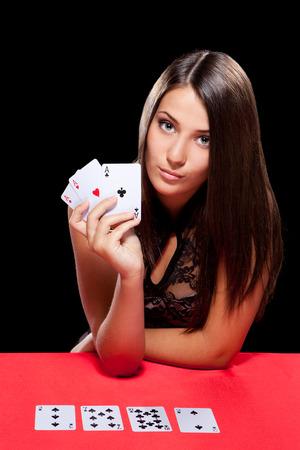 cartas de poker: Mujer joven que juega en los juegos de azar en el casino