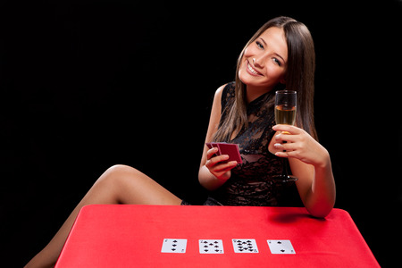 croupier: young girl playing in the gambling on black background Stock Photo