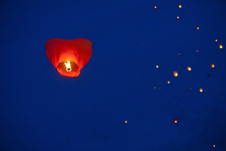 Red heart-shaped chinese lantern in the night sky photo