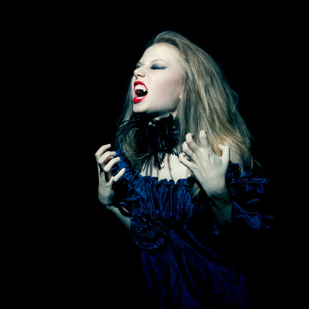 Aggressive vampire waman screaming on black background Stock Photo