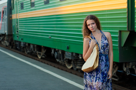 without delay: Young woman waiting train on the platform of railway station Stock Photo