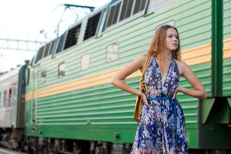 Young woman waiting train on the platform of railway station Stock Photo