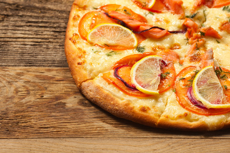 Salmone pizza on old wooden table. With place for text. photo