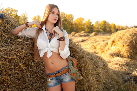 Portrait of woman at the field. Young woman in costume of cowboy looks sideways