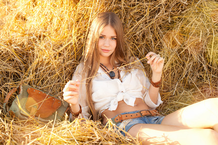 Beauty woman relaxing in the straw in field. Young woman in costume of cowboy looks at camera. photo