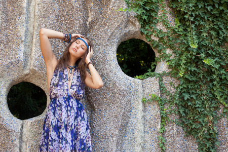 sternly: Young woman in a sundress at the stone wall Stock Photo