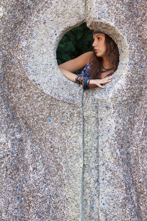 threateningly: Young woman in a sundress at the stone wall Stock Photo