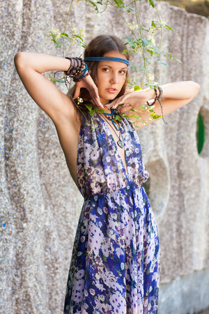 Young woman in a sundress at the stone wall Stock Photo