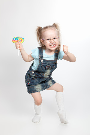 Capricious little girl with big lollipop looking at camers Stock Photo - 29514541