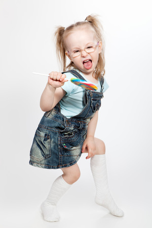 Capricious little girl with big lollipop Stock Photo - 29514425