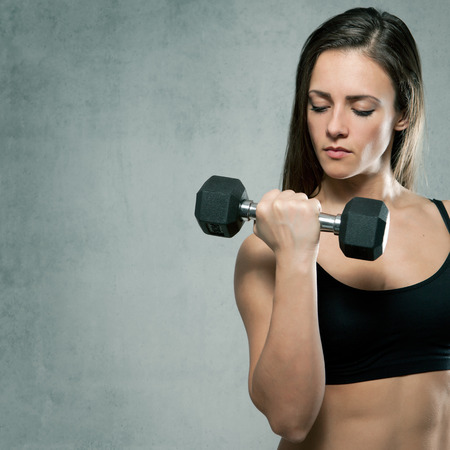 Beautiful sporty muscular woman with dumbbell. On gray background with place for text. photo