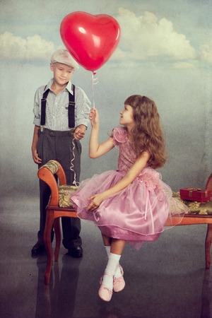 The boy gives a red balloon to the girl. Photo in retro style with old textured paper. photo