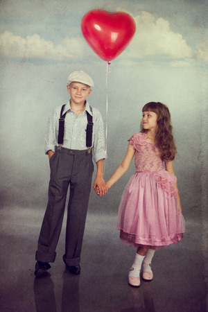 Cute children walk with a red balloon. Photo in retro style with old textured paper. photo