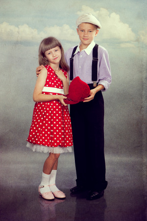 The boy gives beads to the girl. Photo in retro style with old textured paper. photo