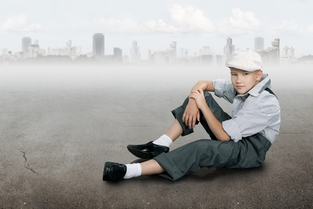 Old fashioned boy looking to the camera and sitting on a ground near city