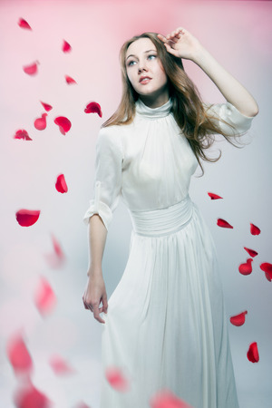 Young beautiful woman with flying red petals of roses photo