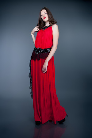 red evening: fashion model in red evening dress posing on gray background Stock Photo