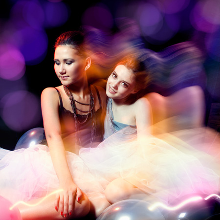 Two beautiful womans in tutu sitting on colorful background photo