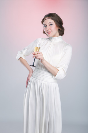 Retro style portrait of beautiful woman with wineglass posing on pink background