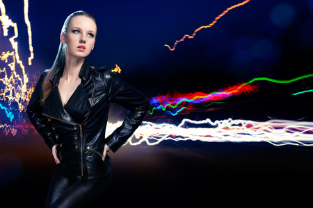 Young beautiful woman in leather jacket on background of night lights photo