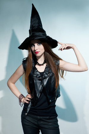belonging to the caucasoid race: Beautiful witch stands and shows hat. Halloween.